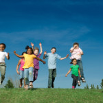 Diverse children running and jumping together on top a hill with the sky in the background. There is some slight motion blur on hands and feet.